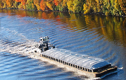 Barge on river passing trees in a variety of fall colors